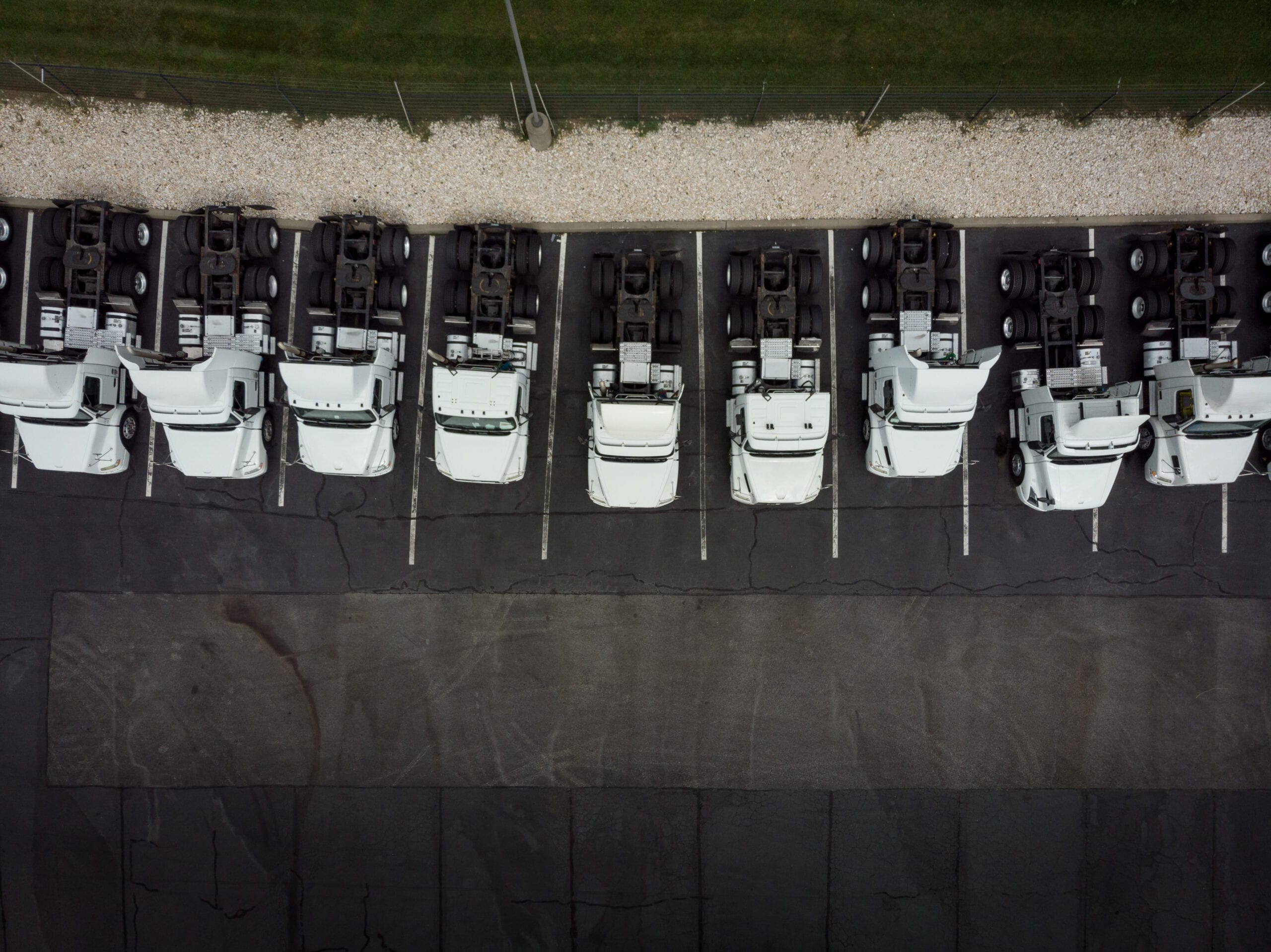 Fleet of white 18-wheeler semi-trucks overhead view drone photography